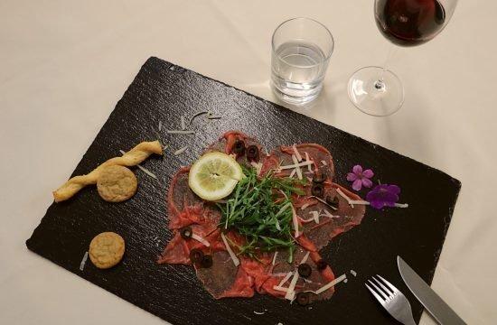 Rindercarpaccio mit Rauke, Parmesanspänen und Oliven